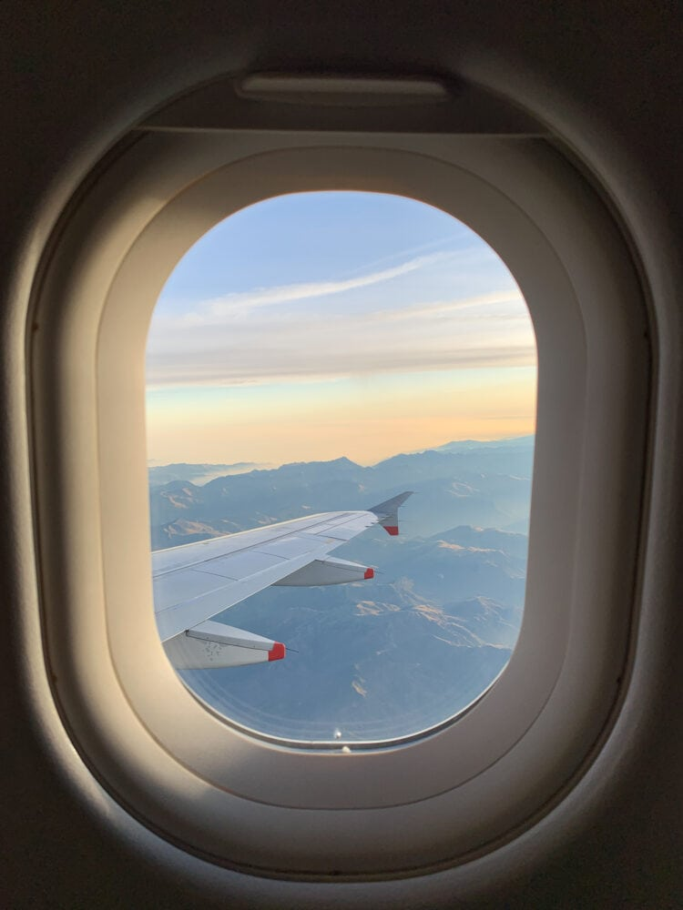 Photo looking out of oval airplane window at tip of the wing of a plane over mountains.