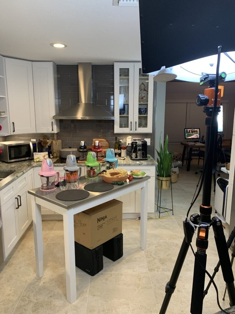 At home camera studio set up in our kitchen with food displayed on the island and lights lighting up the room