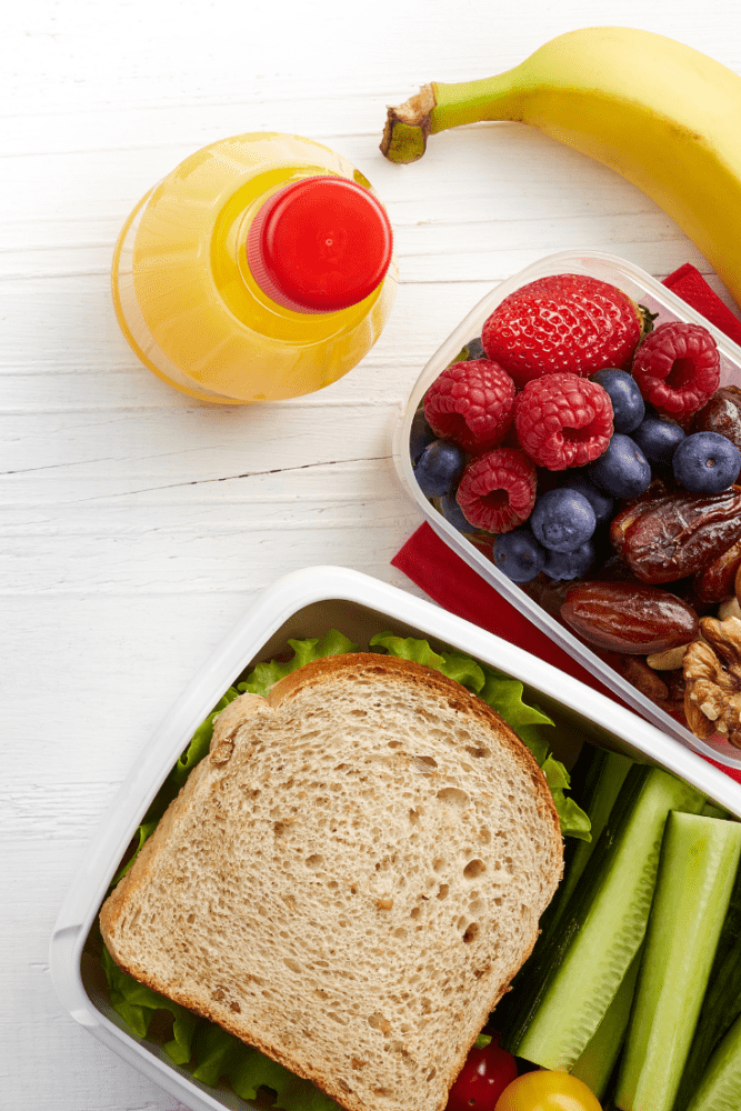 Photo of lunch box with sandwich, orange juice, mixed berries, dates, banana, and cucumber.