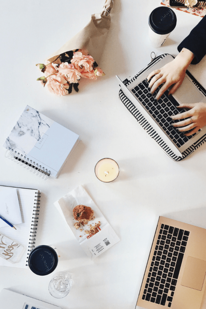 Overhead flatlay shot of at-home desk including two macbooks (a woman's hands typing on one), fresh flowers, planners, coffee, and a candle.