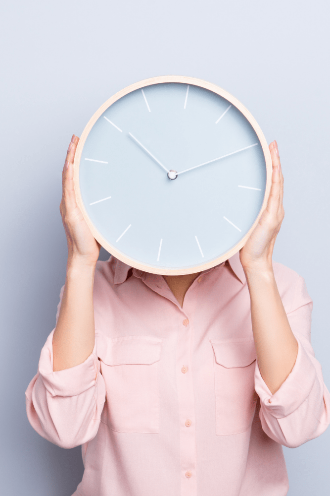 Woman wearing a pink button down shirt holding a big clock in front of her face.