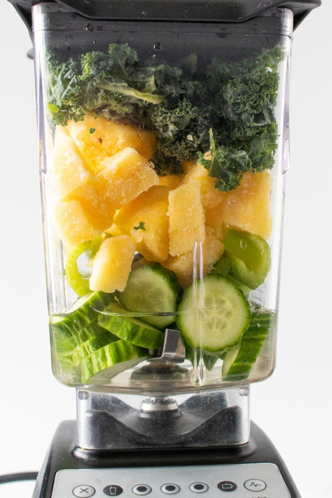 Layered pineapple kale smoothie ingredients in a blender.