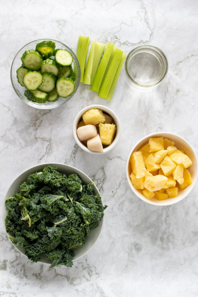 Measuring out the ingredients for the pineapple kale green smoothie including: cucumber, celery, ginger, pineapple, kale, and water.