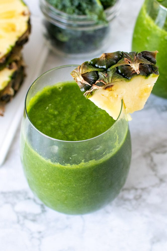 Pineapple Kale Green Smoothie in a stemless wine glass with a wedge of pineapple as garnish.