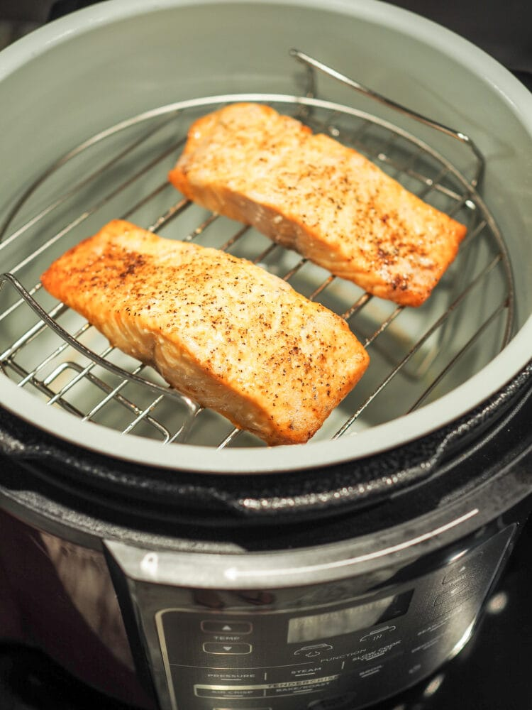 Cooked salmon filets, seasoned with salt and pepper, on a roasting rack inside a Ninja Foodi air fryer.
