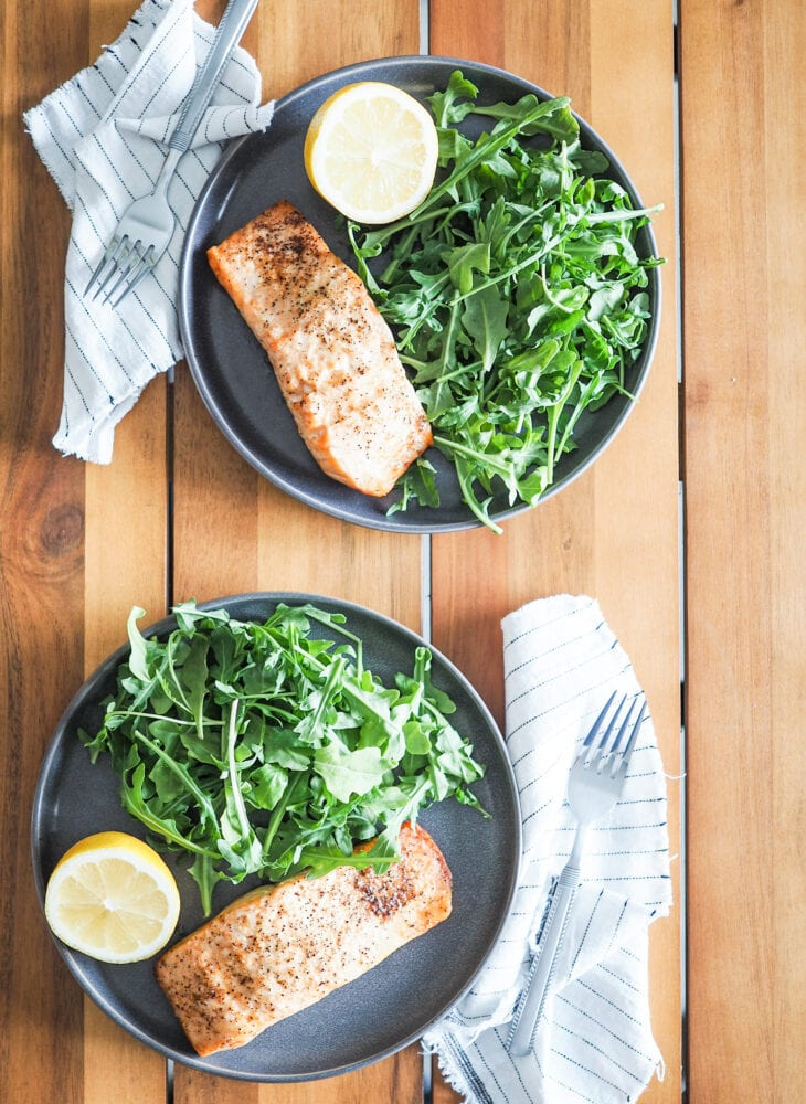 Overhead shot of two gray plates with air fried salmon, arugula, and lemon slices.