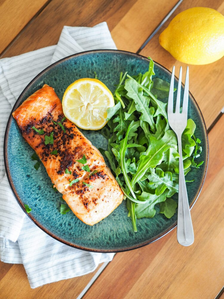 Close up of tajin (chili lime seasoning) on air fried salmon plated on a blue dish with arugula and lemon.