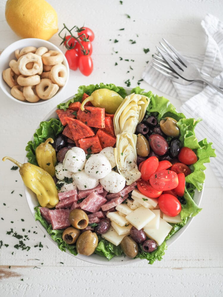 Antipasto Salad with romaine lettuce, salami, soppressata, pepperoncini, olives, mozzarella, provolone cheese, and marinated artichoke hearts. With a side of tarralli crackers and lemon and tomatoes for garnish.