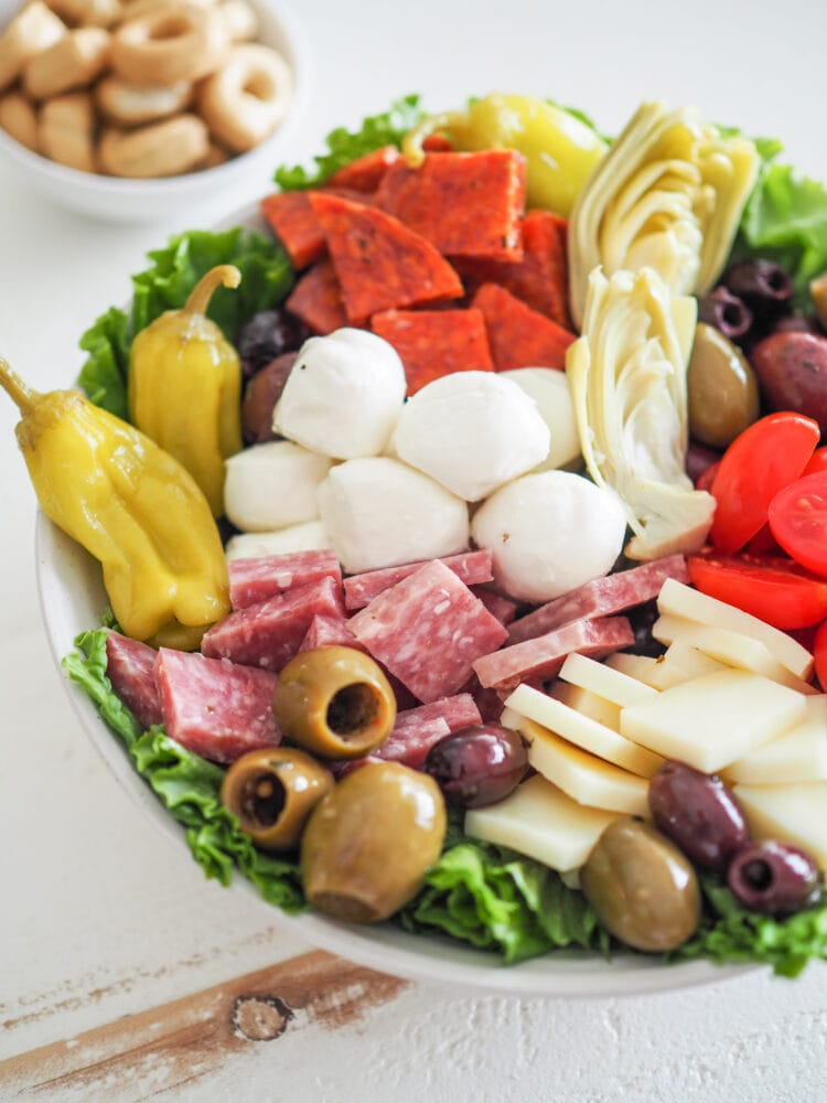 Antipasto Salad with romaine lettuce, salami, soppressata, pepperoncini, olives, mozzarella, provolone cheese, and marinated artichoke hearts. With a side of tarralli crackers.