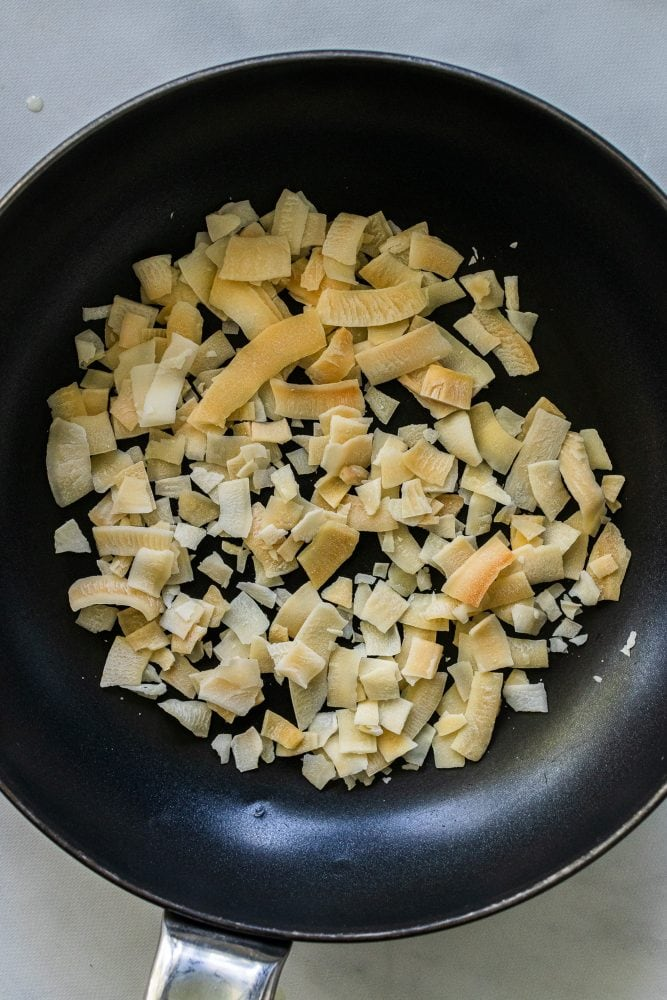 Dry toasted coconut flakes in a non-stick saute pan.