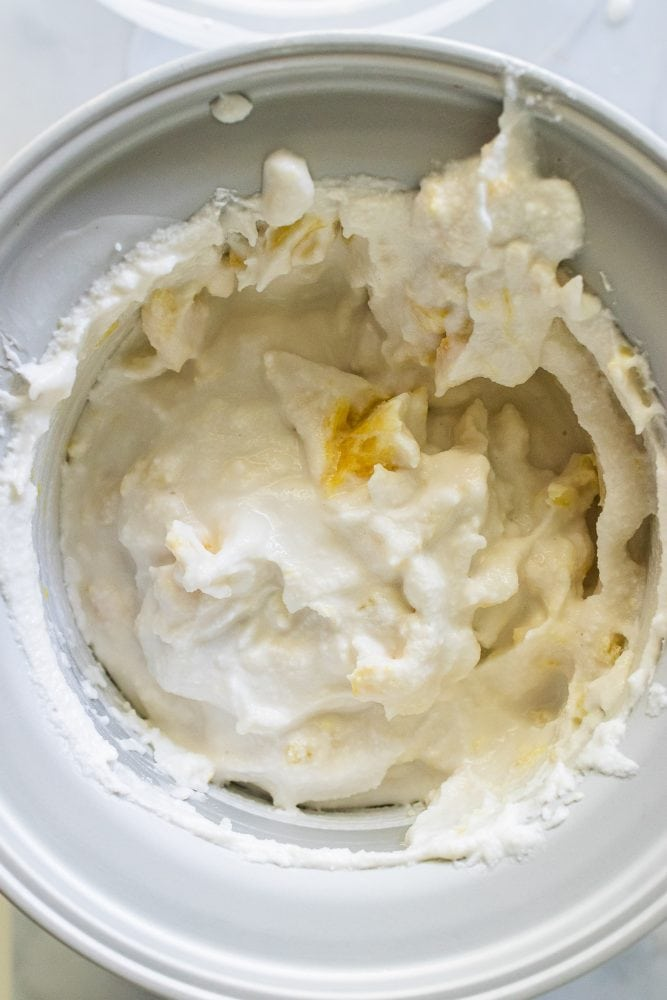 Mixing crushed pineapple into coconut ice cream mixture. The consistency is like soft serve ice cream.