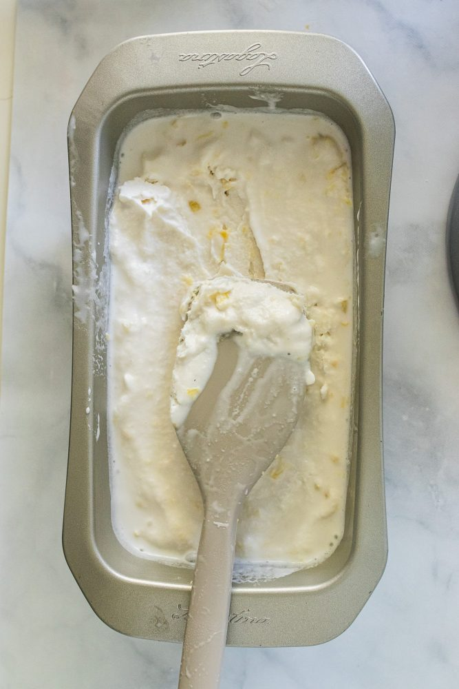 Adding ice cream mixture to a bread loaf pan to put into the freezer to harden.