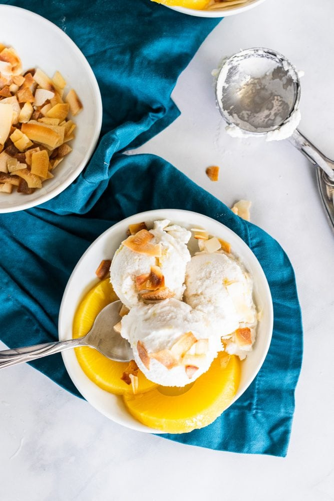 Overhead shot of three scoops of coconut ice cream with toasted coconut and pineapple rings. Bowl is placed over a blue napkin.