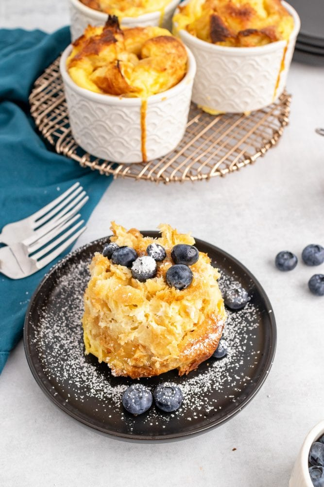 One croissant bread pudding served on a plate, topped with blueberries and powdered sugar.