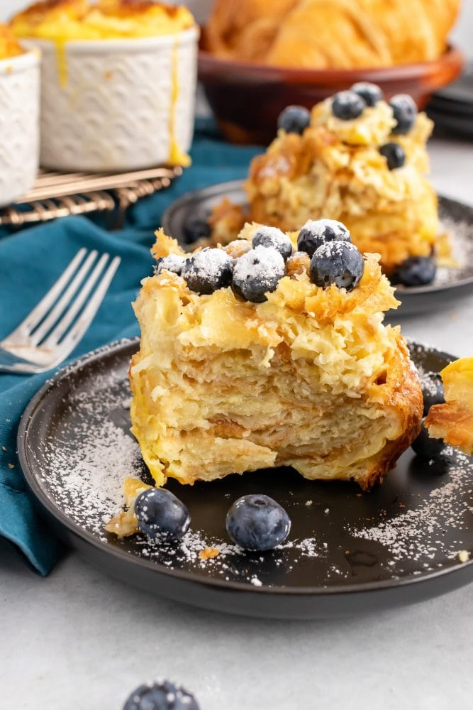 Side view of individual serving of croissant bread pudding showing the flaky layers of croissant, topped with blueberries and powdered sugar.