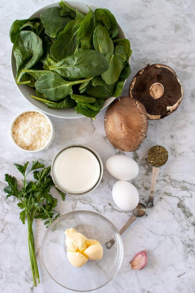 Overhead shot of ingredients to make baked portobello mushrooms: spinach, parmesan cheese, cream, garlic, parsley, eggs, mushrooms, and Italian seasoning.