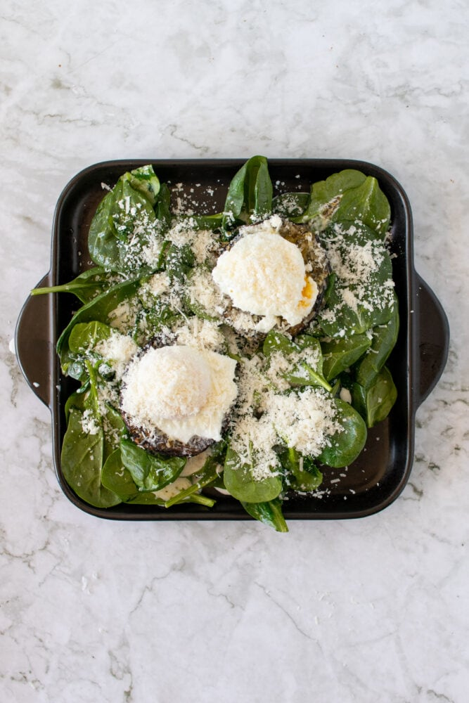 Overhead shot of eggs with parmesan over the portobello mushrooms, before broiling.