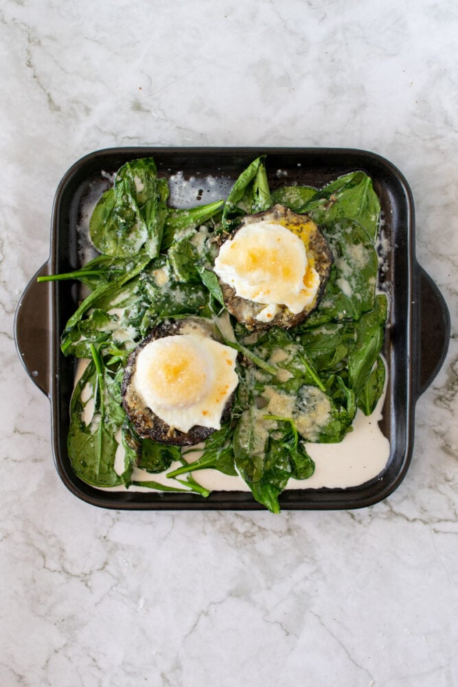 Completed recipe for stuffed mushrooms: Overhead shot of eggs on mushroom caps over a bed of spinach.