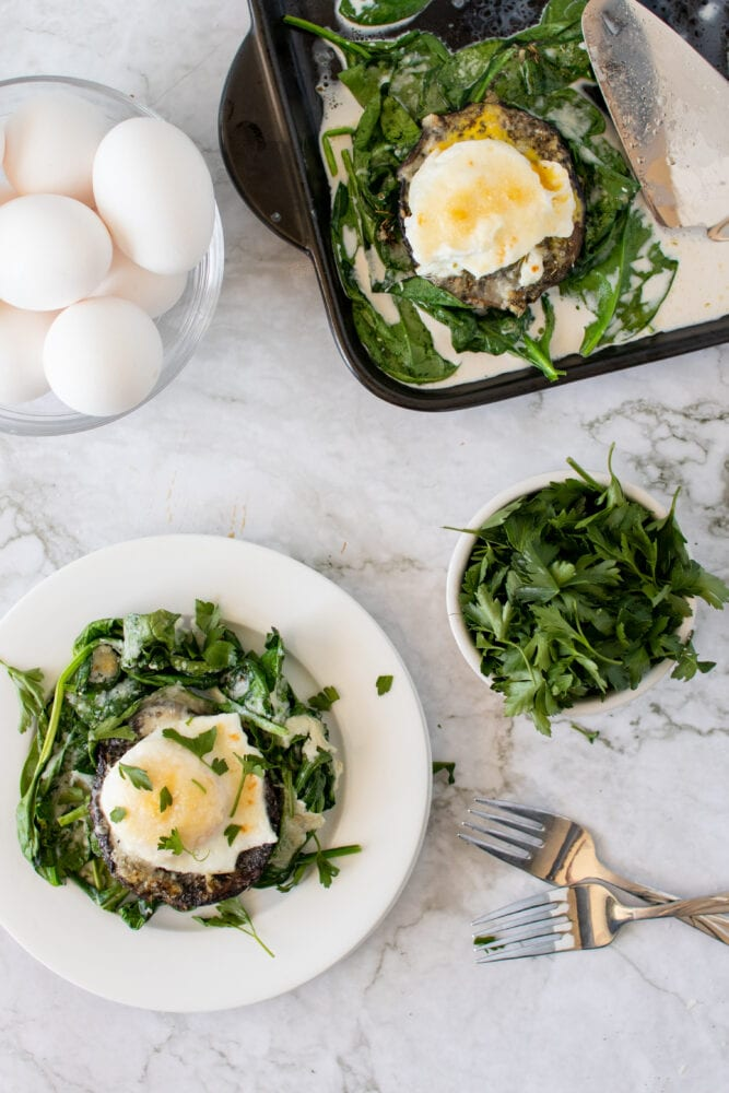 Overhead shot of eggs and baked portobello mushrooms on a bed of spinach