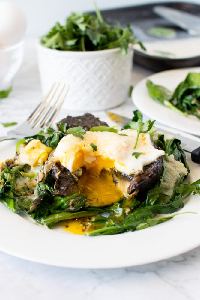Final shot of baked portobello mushrooms with a bite taken and runny egg yolk mixing with the sauce and spinach.