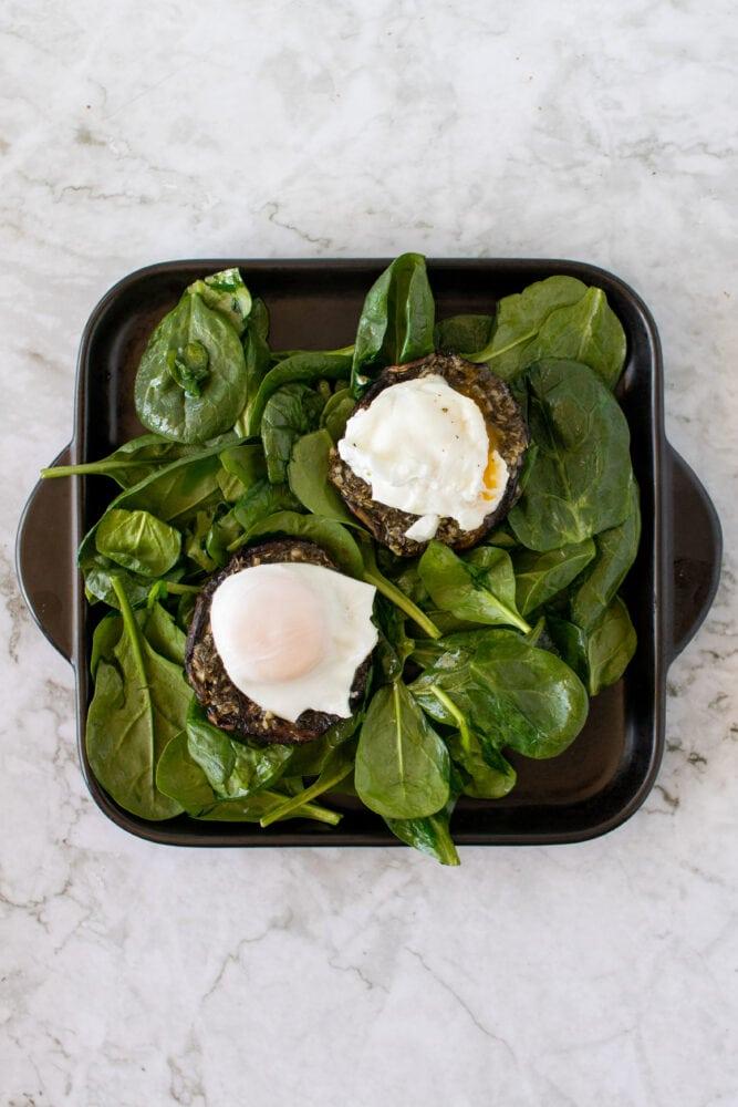 Overhead shot of eggs on portobello mushrooms and spinach.