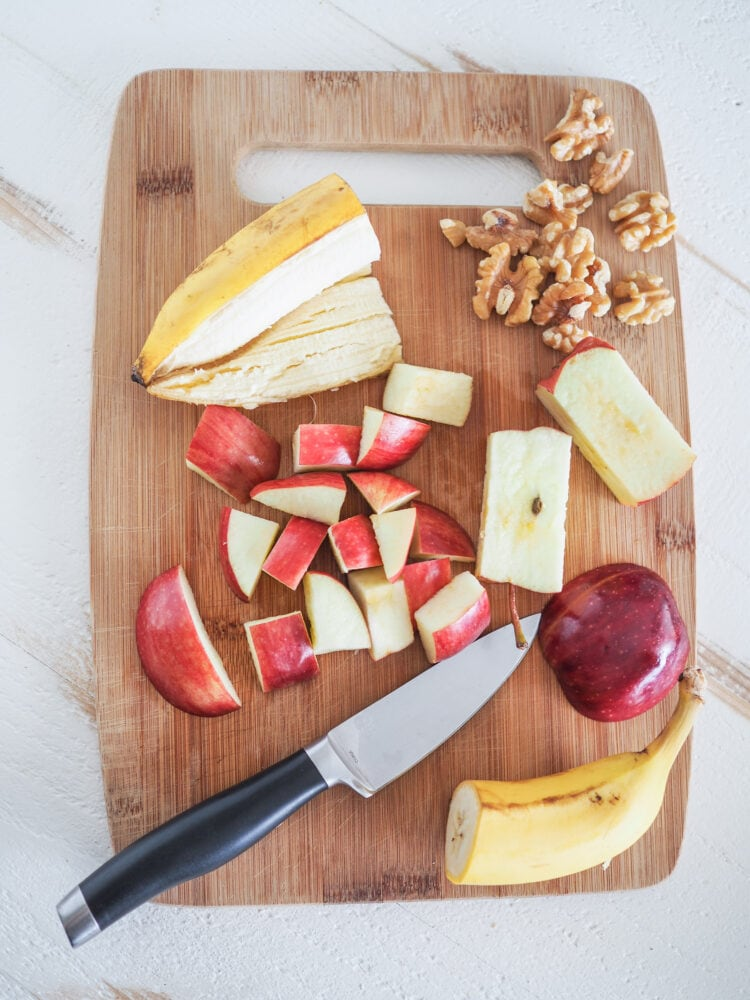 Bamboo cutting board showing some of the apple smoothie ingredients including half a banana, chopped apple, and walnuts.