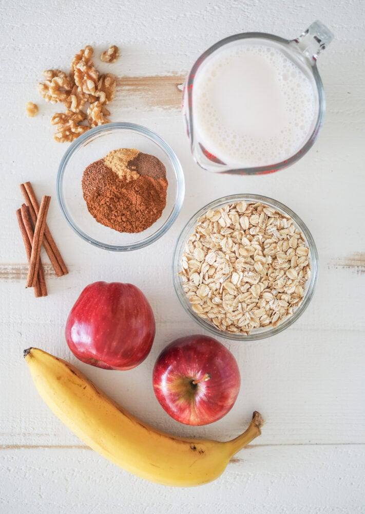 Overhead shot of apple smoothie ingredients including walnuts, oat milk, spices, oatmeal, apples, and banana.