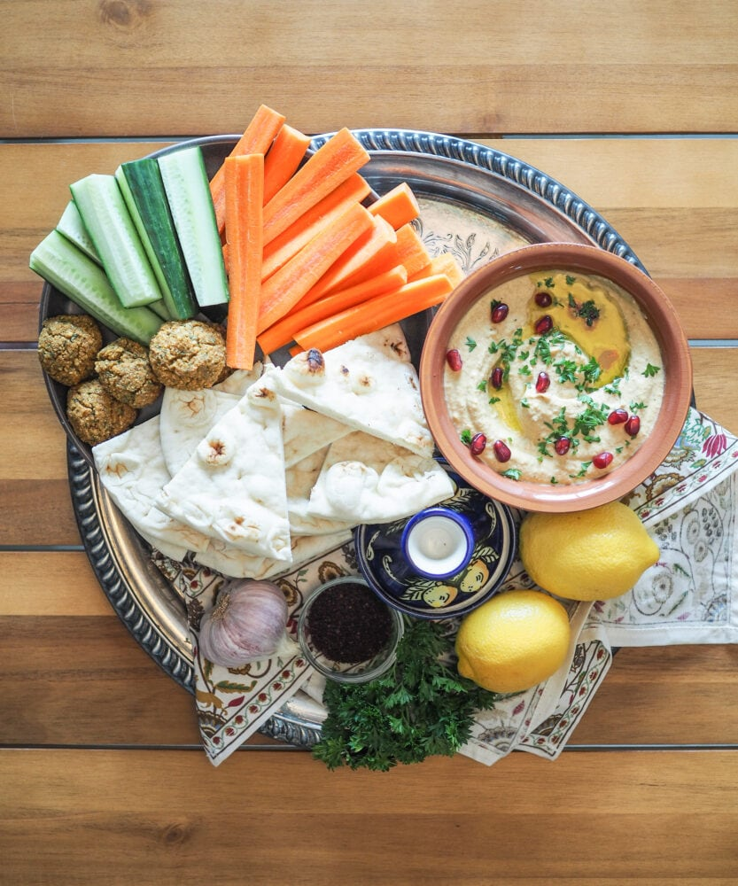 A mezze platter with cucumber, carrots, falafel, naan, and baba ganoush. Also, for decoration, garlic, lemon, parsley, and a blue tagine.