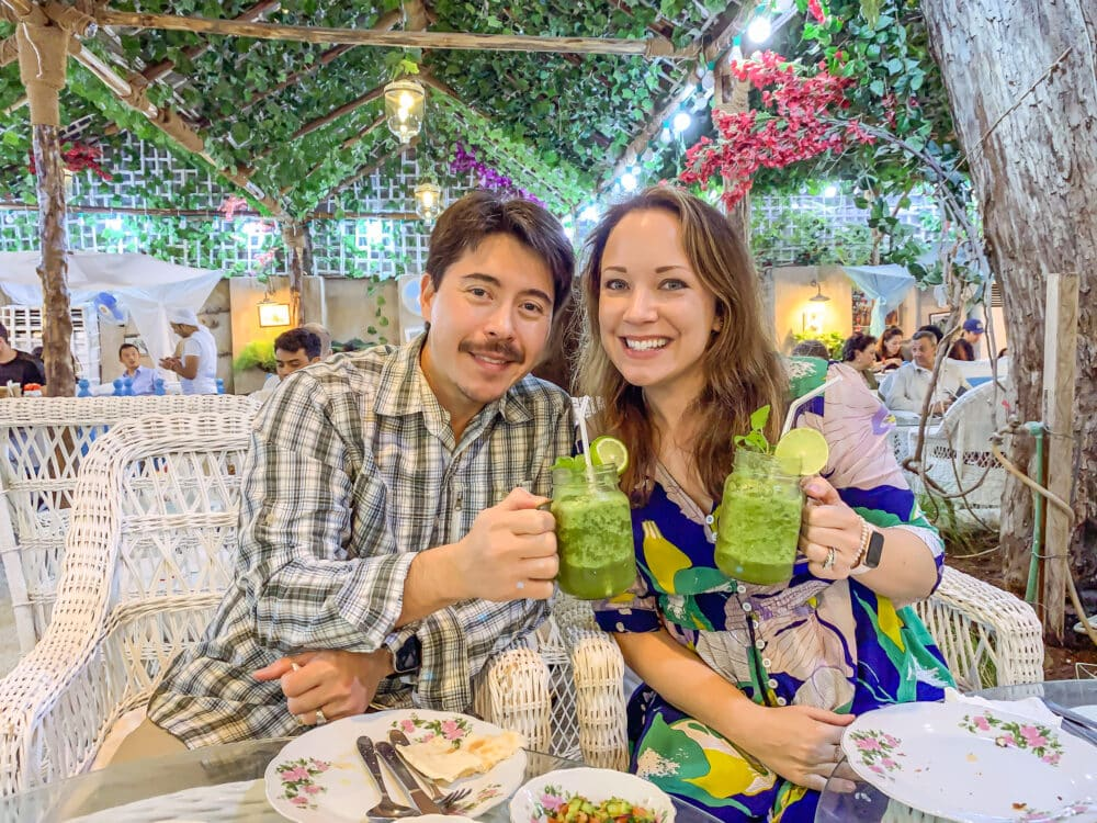 Pete and Rachelle at a restaurant in Dubai, toasting with mint lime smoothies.