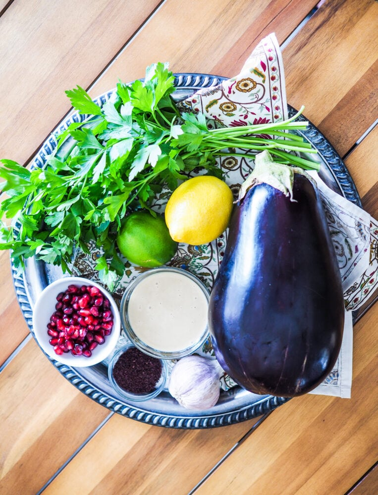 A platter showing some of the ingredients used to make baba ganoush including a whole eggplant, lemon, lime, tahini, garlic, and pomegranate, sumac, and fresh parsley.