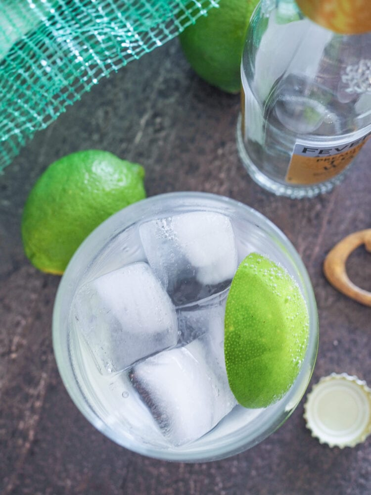 Overhead photo of a single gin and tonic garnished with lime, and limes and tonic bottle in the background.
