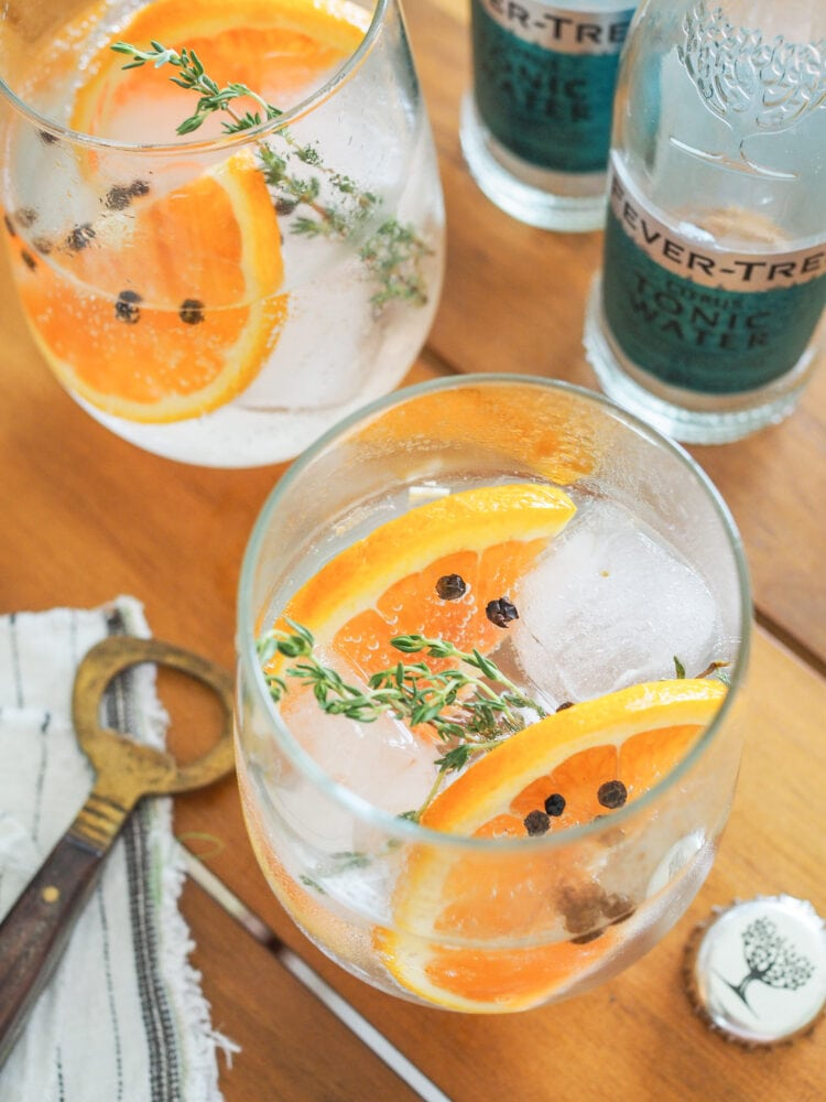 Gin and tonics garnished with orange slices, thyme, and peppercorns.