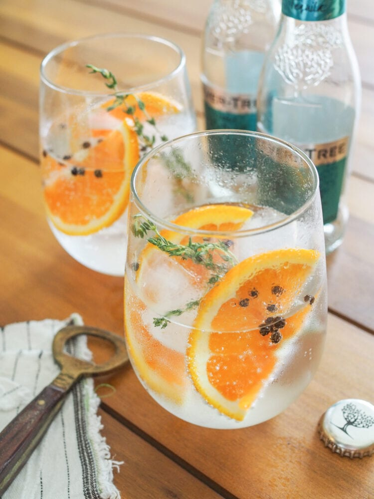 Two gin and tonics garnished with orange slices, thyme, and peppercorns.