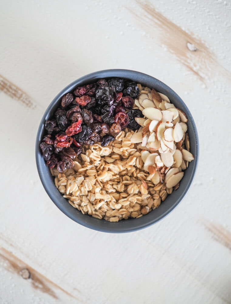 Overhead shot of microwave oatmeal with dried berry mix and almond slices.