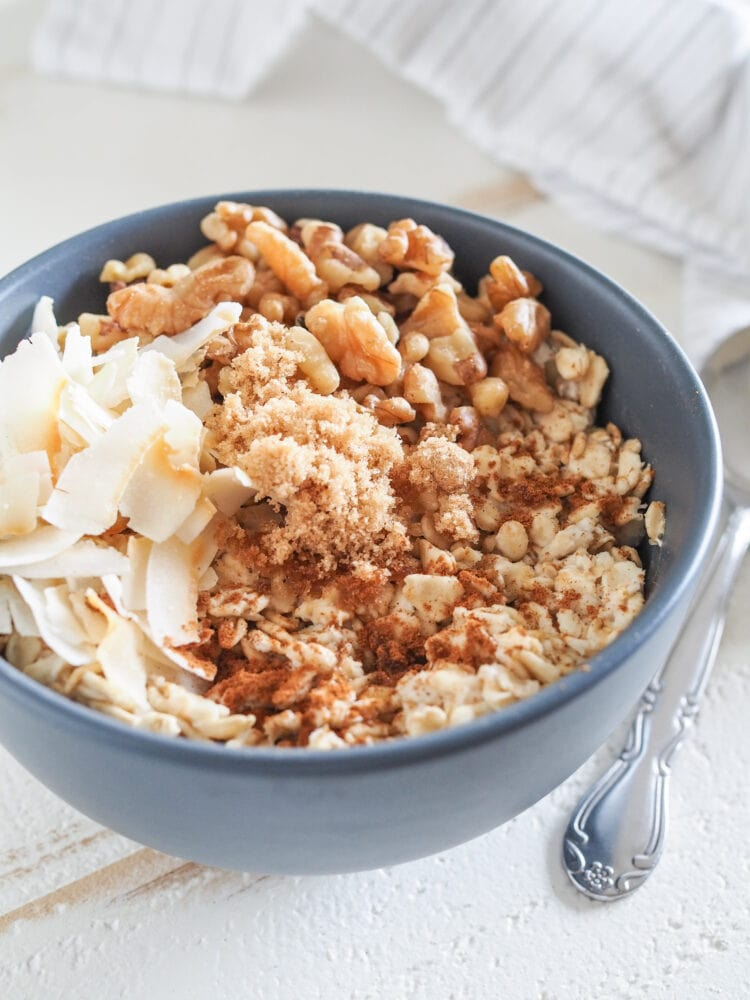 Bowl of microwave oatmeal in a blue bowl on a white table. Toppings include toasted coconut, brown sugar, and walnuts.
