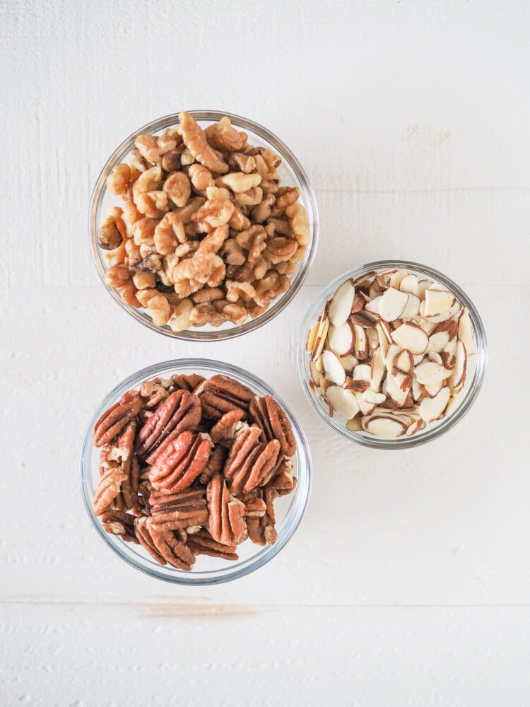 Overhead shot of nuts in prep bowls: walnuts, pecans, sliced almonds.