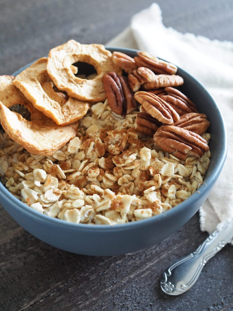 Bowl of microwave oatmeal on wood table with dried apple slices, pecans, and cinnamon.