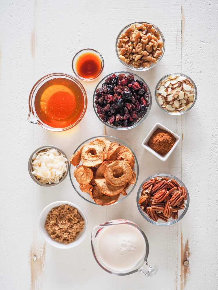 Overhead shot of microwave oatmeal toppings in prep bowls including: vanilla, honey, dried berries, walnuts, almond slices, shaved coconut, dried apples, cinnamon, pecans, brown sugar, and milk.