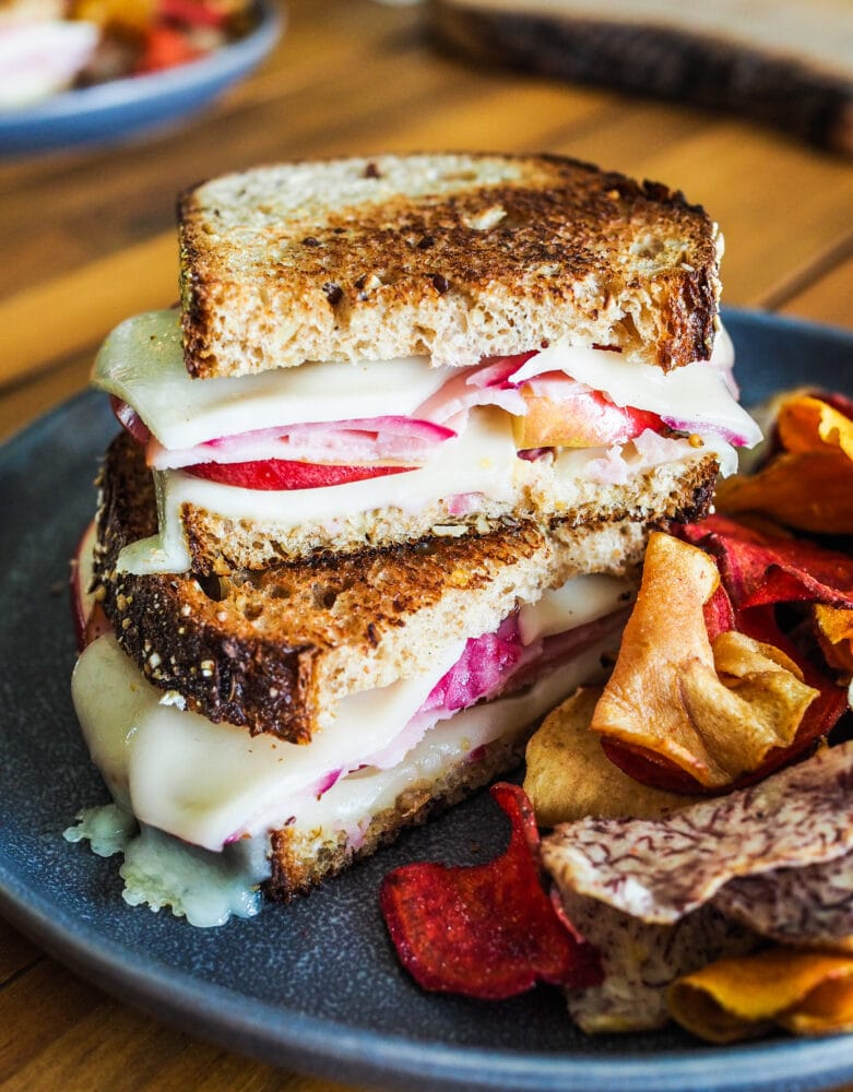 Stacked ham and cheese sandwiches with apples and pickled red onions served with orange and red root vegetable chips.