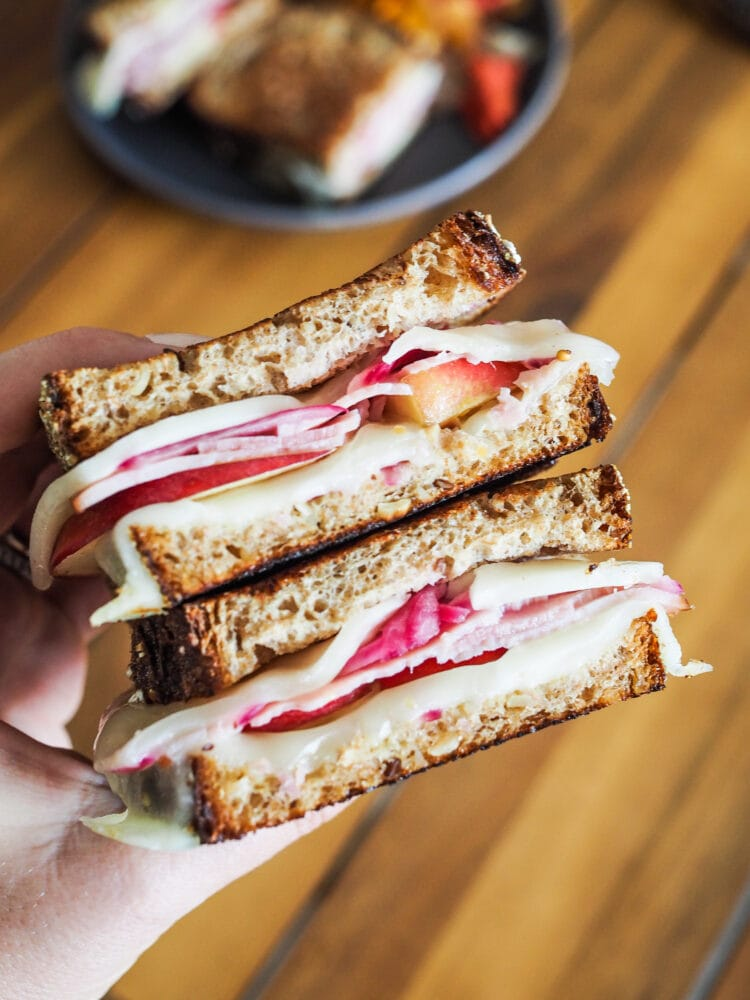 Hand holding two servings of ham and cheese sandwiches with apples and pickled red onions