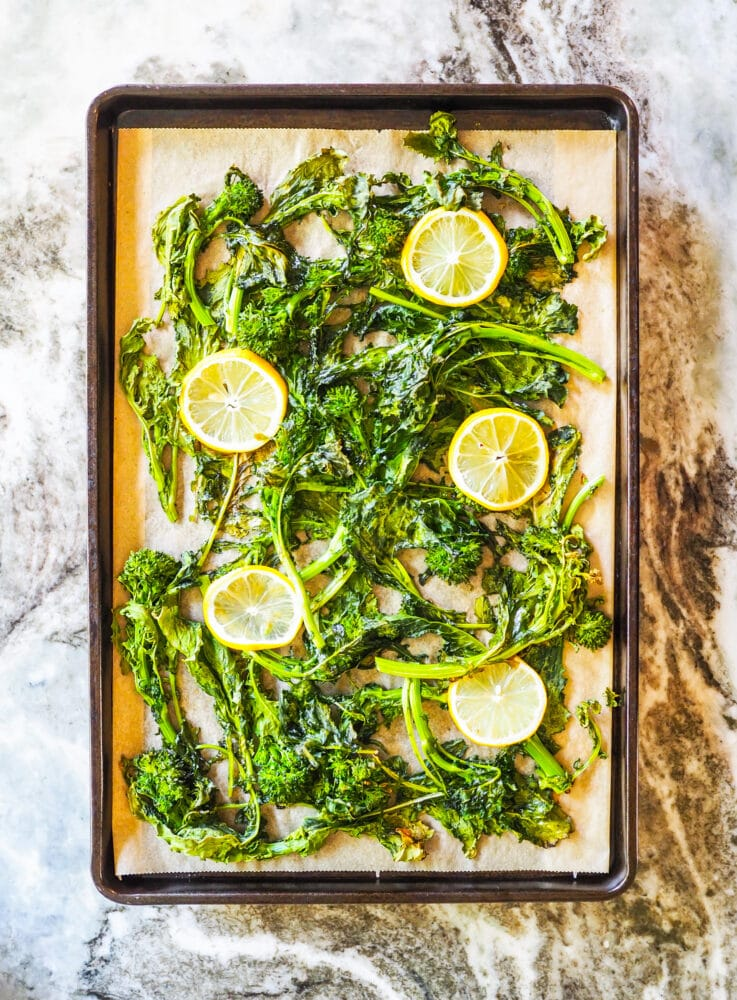 Rapini on a sheet pan after roasting in the oven.