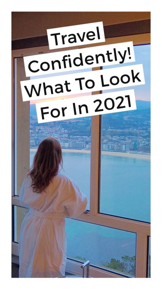 "Girl wearing a robe looking outside of hotel window at a coastline with overlay text that reads, ""Travel Confidently! What to look for in 2021"""
