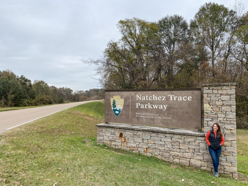 Rachelle standing next to the sign for the start of the Natchez Trace Parkway.