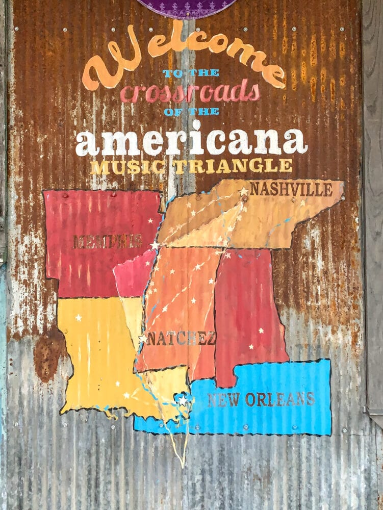 """A rustic map on corrugated metal featuring Arkansas, Louisiana, Mississippi, Tennessee, and Alabama, showing the cities of Memphis, Nashville, and Natchez with stars. The sign says, """"Welcome to the crossroads of the Americana music triangle."""""""