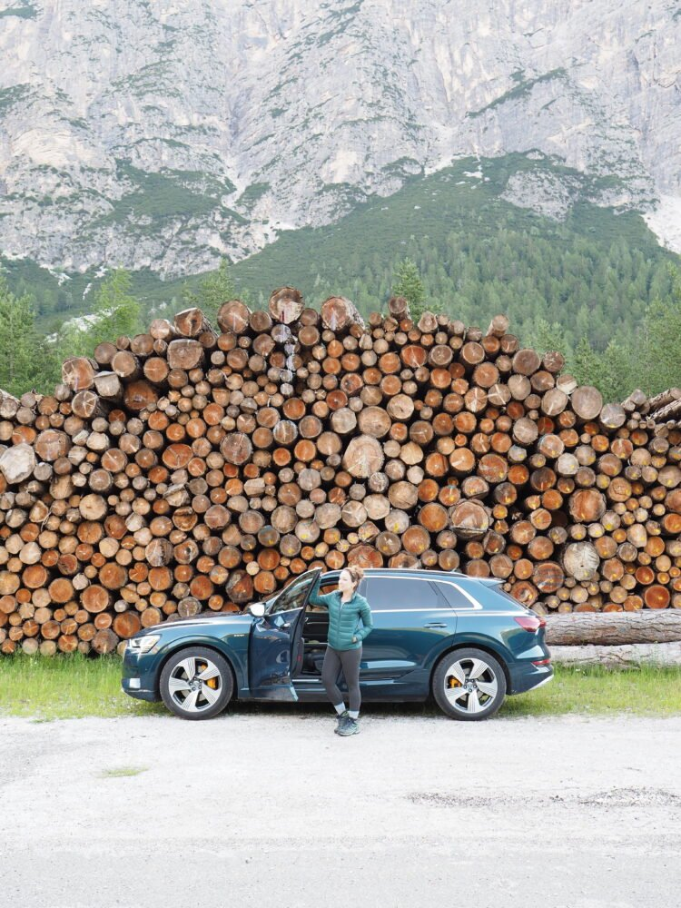 Rachelle wearing a puffer jacket and leggings, standing outside an SUV parked in front of stacked logs.