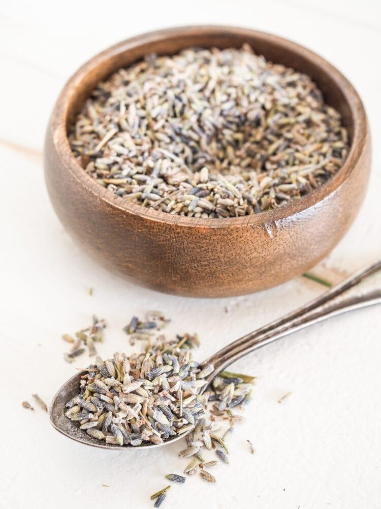 A small bowl and spoon filled with dried lavender buds.