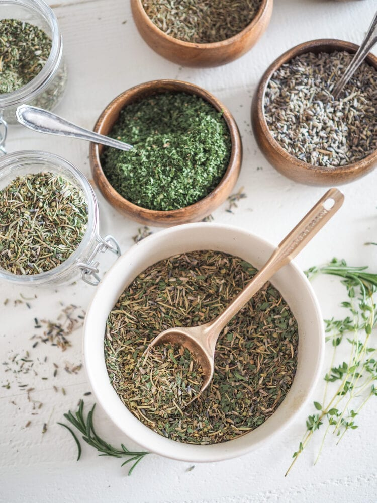 Blending herbs de Provence in a large bowl, with individual smaller bowls of spices surrounding it.