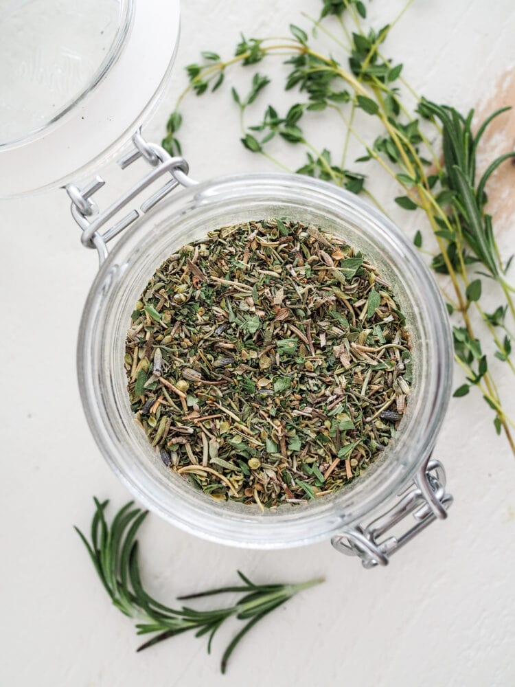 Overhead shot of a glass jar filled with herbs de Provence.