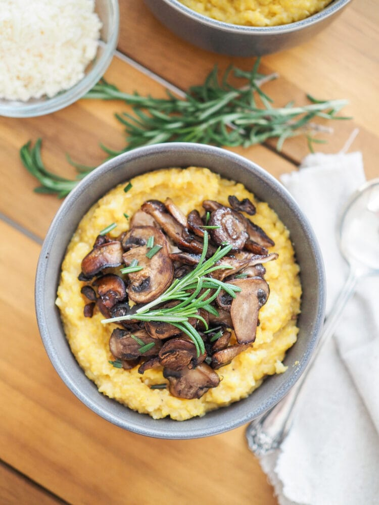 Overhead shot of a wood dining table with a bowl of yellow cornmeal polenta topped with sautéed mushrooms and a fresh spring of rosemary. There's a bowl of Parmigiano-Reggiano cheese on the side.