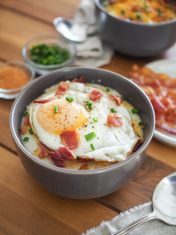 A bowl of grits topped with a fried egg, bacon bits, chives, and salt and pepper.